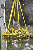 Hanging Easter basket with Salix wreath filled with Easter eggs