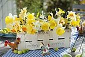 Easter table decoration with daffodils on the terrace