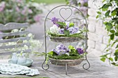 Etagere with baskets and heart motifs, filled with syringa flowers