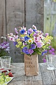 Small bouquet of perennials and summer flowers in a printed paper bag