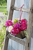 Wooden basket with fragrant rose tied to old wooden ladder