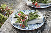 Napkin decoration with vegetables and herbs, beans and flowers