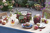 Table decoration with apples (Malus) and ornamental apples in wire baskets