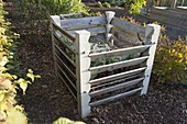 Composter with concrete posts and boards, path with bark mulch