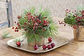 Small bouquets made of pinus (pine) and roses (rosehip)