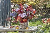 Autumn bouquet with perennials and fruits in basket vase