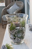 Glass in glass Advent decoration with candle, white colored pine cones