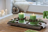 Small Advent decoration, green candles with garlands of star anise