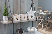 Lanterns with star decoration hanged on board on wall