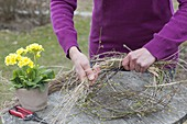 Easter table decoration with wreath of twigs, grasses and yellow primrose