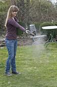 Woman sprinkling Terra preta (black earth) as soil activator