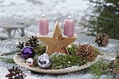 Flat bowl with wooden star, candles, moss, baubles