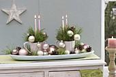 Adventsgesteck in Tassen auf Brotschale, dekoriert mit Christbaumkugeln