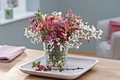 Small Hyacinthus flowers and branches bouquet in glass vase