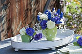 Small bouquets in cups on wooden tray