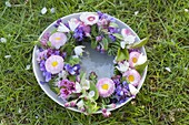 Colorful spring wreath in cup with water in the grass