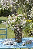 Malus (ornamental apple) branches bouquet in basket with glass vase