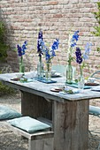 Laid table with delphinium (larkspur) in bottles