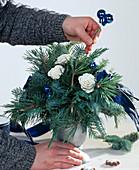 Weihnachtsstrauß binden: 4. Step. Kugeln in Strauß stecken.