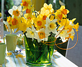 Bouquet with various daffodils in green glass vase