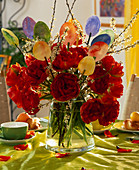 Easter bouquet with filled tulips, cherry branches and self-painted paper eggs
