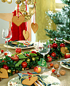 Table decoration with gingerbread hearts and garland made of branches and balls