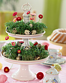 Easter table decoration, cake stand made of porcelain with cut-out cress