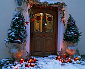 House entrance Christmassy decorated with amphorae, branches