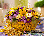 Sisal basket with late summer arrangement of asters and sun hat