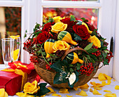 Basket with autumn arrangement of roses, ornamental gourds and berry decorations