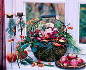 Metal basket lined with moss and decorated with flowers and branches