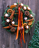 Door wreath made of twigs, cinnamon stars, cinnamon sticks, cones and ribbons