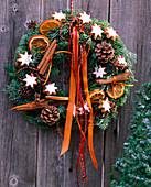 Türkranz aus Zweigen, Zimtsternen, Zimtstangen, Zapfen und Bändern