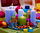 Colorful candles on plate with Christmas decoration