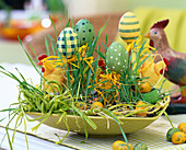 Easter bowl with wheatgrass, eggs, chicken and raffia