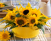 Yellow tin cup with Helianthus annuus (sunflowers