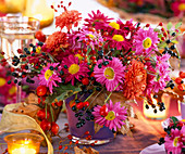 Chrysanthemum, rose Rosehips, Ligustrum Privet berries in Purple Glass Mug
