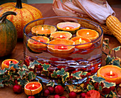 Cucurbitta pumpkins hollowed out as a floating candle holder in glass bowl