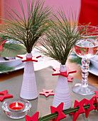 Pinus strobus-silk pine in white vases, red wooden stars, red tealight
