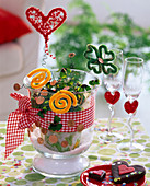 Oxalis deppei 'Iron Cross' in glass vase with ribbon, copper money