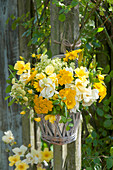 Yellow bouquet in wicker vase hung on posts