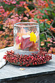 Lantern with colorful leaves in roses (rosehip) wreath