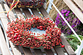 Wreath made of roses (rosehip) with bowl placed on bench