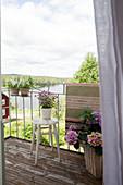 Balkon mit Hortensien mit Blick auf sommerliche Landschaft und Fjord