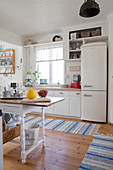 Retro fridge an blue-striped rugs in country-house kitchen