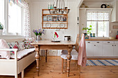 Old wooden table in cosy, country-house-style kitchen-dining room