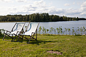 Two deckchairs on grass next to lake