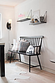 Black bench with scatter cushions below two shelves of crockery on wall