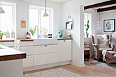 White fitted kitchen with open doorway leading into living room