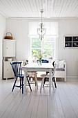 Verschiedenfarbige Windsorstühle um den Tisch im hellen Esszimmer